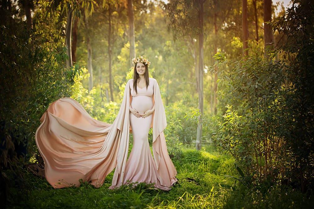 צילומי הריון בטבע עם תאורה טבעית, רכה ומחמיאה בשילוב שמלת הריון בצבע וורוד עתיק
