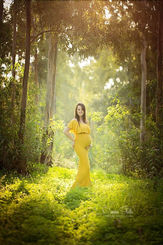 צילומי הריון בטבע עם תאורה טבעית, רכה ומחמיאה בשילוב שמלת הריון בצבע צהוב