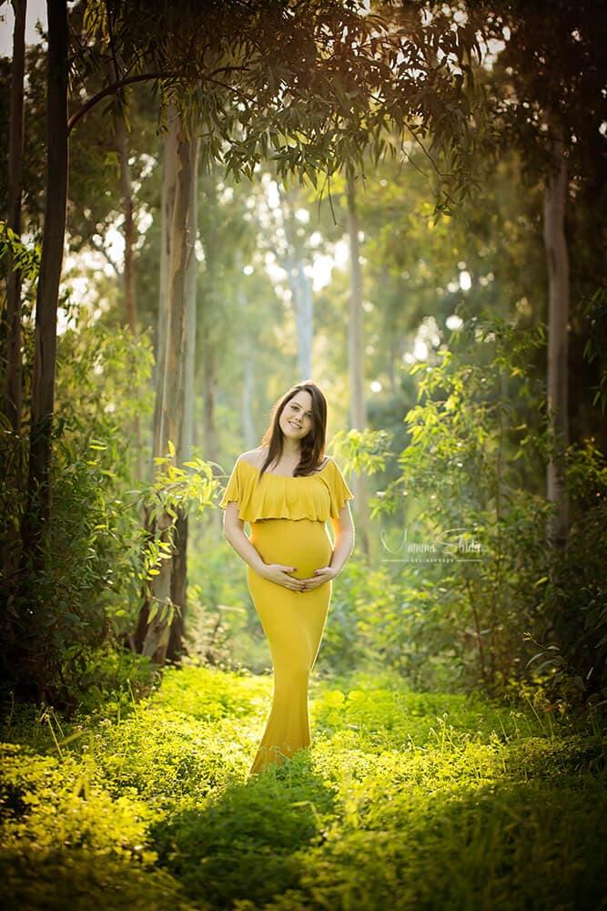 צילומי הריון בטבע עם תאורה טבעית, רכה ומחמיאה בשילוב שמלת הריון בצבע חרדל